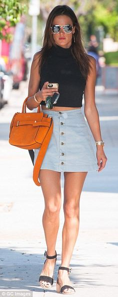 Pop of colour: Alessandra brightened up her look with a tangerine handbag...