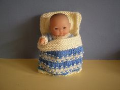 """This knitted cradle, complete with a set of matching bedding, will fit a 5"""" baby doll or similar size toy. The sides of the cradle fold up over the doll to make a bag and drawstrings keep everything safe inside. An ideal present for a child who can't leave home without a doll."""