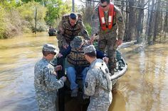 Members of the Louisiana National Guard's 2225th Multi-Role Bridge Company, 205th Engineer Battalion, help a man out of the bridge erection boat they used to check on residents who could not get out of their homes, in Ponchatoula, La., March 13, 2016. The current of the river, which had overcome its banks and flooded the road, was too strong for regular boat motors to battle. Louisiana National Guard photo