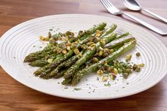 Warm tender roasted asparagus with crispy and piquant capers and pistachio garnish