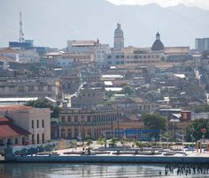 This view of Santiago de Cuba was taken as our ship was coming into the harbor. A park-like plaza can be seen in the foreground. The twin spires of the Cathedral of Our Lady of the Assumption, which is located in the town center, can be seen toward the top center of the photo. Destination: Cuba | February 2017 | Text and photos by Rochelle A. Shenk | #Cuba #Santiago de Cuba #Harbor