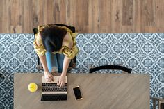Top view of young asian woman sitting, using laptop in modern workplace, café coffee shop. Urban female college lifestyle concept on wooden table, blue vintage floor tile pattern with copy space. Coffee Shop, Tile Floor Diy, Tiled Hallway, Wedding Card Design, Urban, Modern Room, Wooden Tables, Tile Patterns, Top View