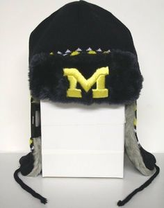 NCAA Michigan Wolverines Team Trapper Knit (Navy/Gold, OSFA) by New Era. Save 25 Off!. $14.99. Sherpa. Official team logo in raised embroidery on the front. New Era Team Trapper Knit Hat.Keep warm and in style with this knit trapper hat. Features include an embroidered team logo at front, a stitched New Era flag at wearer's left side, and a diamond pattern print. Sherpa lined and insulated with double ties at neck for added comfort.