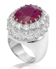 A ruby and diamond ring  Centrally set with an oval mixed-cut ruby, within a brilliant and marquise-cut diamond surround, mounted in 18k white gold, the ruby estimated to weigh approximately 11.20 carats in total, the diamonds estimated to weigh approximately 7.30 carats in total