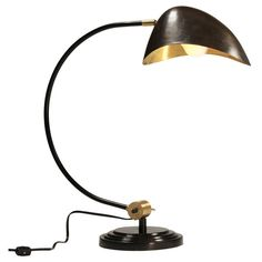 A sleek yet classic brass and dark metal table lamp with a curved neck. - Dimensions: x x - Materials: Metal - Finish: Brass; Dark Metal This item typically ships weeks from time of