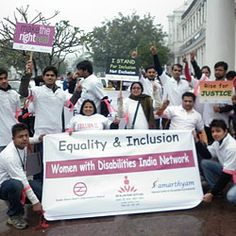Several men and women, some in wheelchairs, in India cheer and hold a large banner that reads Equality & Inclusion Women with Disabilities I...