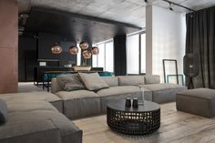 This large apartment uses a popular color palette of grey on grey with varying shades (not quite 50) of that cozy and calming color. The soft gray sofa features large overstuffed cushions that are just as inviting as any mass-market sectional. The heavy, soft curtains mean that it can be movie night at any time of day.
