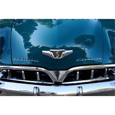 """The late summer sky and shade trees reflect in the teal green paint on the hood of a handsome early 1950s Studebaker Champion in this 5x7 classic car photo. The chunky """"S"""" logo resting on golden shiel"""