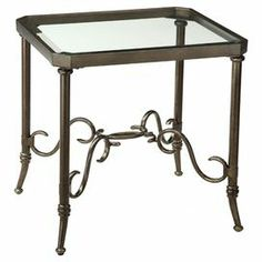 """Glass-topped end table with a scrolling cross stretcher.     Product: End tableConstruction Material:  Metal and glass  Color: Antique bronze Features: Beveled glass top  Graceful arched scroll cross stretcher        Dimensions: 24""""  H x 25""""  W x 22""""  D"""
