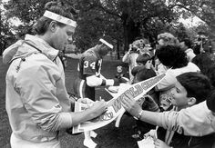 Jim McMahon and Walter Payton sign autographs for fans during training camp at…