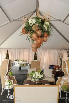 Amazing floral chandelier by http://www.intrigue-designs.com adds drama to this eco-chic wedding lounge completed with burlap domchairs and linen accent chairs with white washed wood and pewter tables.  The mercury glass centerpiece with mirror cubes white hydrangea, ranunculous and a variety of grey toned greens created a warm stmosphere.  The custom bar with burlap end caps finished the look with moss sculptures.  Swooning over this suspended floral arrangement hanging…