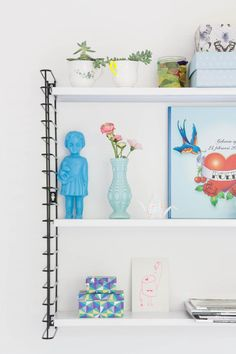 20 Ways to Decorate With Flowers For Spring - white shelf with decorative objects in shades of blue with a pop of pink flowers and green plants