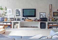 Embutida na estante de alvenaria, a lareira decora e aquece a sala.