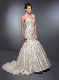 Private Label By G - Style 1465. A gorgeous lace gown fully adorned in superb beadwork/embroidery, creating an elegant pattern of 3D floral decor that lays over English net and is then finished with a corset back and beautiful semi-cathedral train.