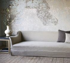 A gorgeous sofa with pure clean lines, a winter bouquet and the [amazing] texture of the raw wall.