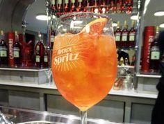 Für den Original Aperol Spritz zunächst ein Weinglas mit Eiswürfeln füllen (bedeckt, aber kein Berg über dem Glas). Dann in das Glas Prosecco