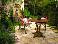 Biddlestone Cottage Garden - the perfect outdoor space, with stone paving, a water feature and a small bistro table