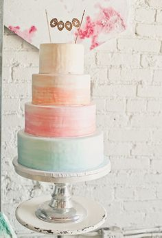 A four-tiered watercolor orange, pink, and blue wedding cake | Brides.com