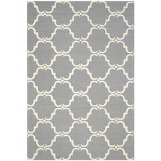 Stylishly anchor your living room or master suite with this elegant hand-tufted wool rug, showcasing a trellis-inspired pattern in dark gray and ivory.