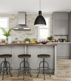 Keep tradition cool with an updated kitchen look. Pale gray base and wall cabinets anchor a wash of beige tile and flooring in natural materials for an organic feel. The big pendant lamp is meant to make a statement, so that everyone gathers at the island underneath.