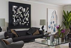 elegantes Wohnzimmer mit schwarzem Ledercouch und künstlerischen Bildern