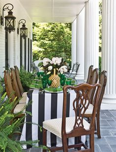 Black and white striped tablecloth, green tabletop, magnolias, brown cane back chairs - great mix