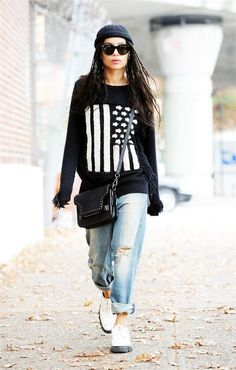 Zoe Kravitz wears a Coach Flag Intarsia Sweater with distressed boyfriend jeans, loafers, a beanie and a black studded bag.