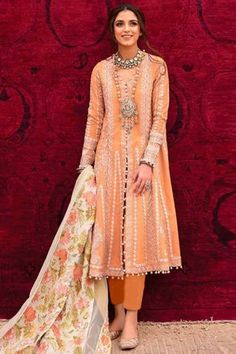Smartly designed for women on the go, this coral peach cotton trouser suit which comprises an elegant ethnic look. This v neck and full sleeve clothe designed using thread work. Accompanied by a matching santoon cigarette pant in coral peach color and off white net dupatta. Cigarette pant is plain. #trousersuit #salwarkameez #malaysia #Indianwear #Indiandresses #andaazfashion