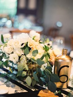 Golden bottle as table number (Escort Card & Table Number Calligraphy: Steele My Heart + Wedding Planning, Styling + Floral Design: Lovely Little Details - Classic Charles Krug Winery Wedding captured by Jessica Burke