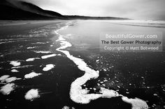 """Rhossili Bay by Matt Botwood. """"A dark and damp day not really conducive to photography, but the contrast of  the surf with the dark cliffs below Rhossili Down caught my eye and opened  up the possibility of a striking mono image."""""""
