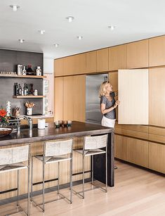 Modern Connecticut summer home renovation with japanese elm cabinets, Calacatta marble, and concrete countertop island in the kitchen