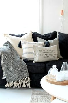 Layering light, neutral cushions and throws will lighten up the room and also make it feel cosy and inviting