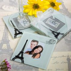 "Eiffel Tower Wedding Coaster Set includes two glass coasters. They feature a white background printed with a black Eiffel tower and a post mark that reads ""From Paris with Love"". Each one has a central photo window. They come packaged in a clear acetate gift box. It is wrapped in a white organza ribbon tied into a bow on top."