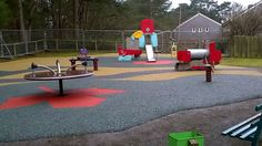 Different colours of rubber mulch can be used to create patterns within the safety surface.   This playground also uses red wet pour under some play equipment