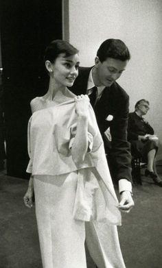 1956 – Parigi, Francia – Lo stilista Hubert de Givenchy sistema un abito disegnato per Audrey. L'attrice ha preteso nella produzione di Cenerentola a Parigi che fosse lui a realizzare i suoi abiti. Tra i due nascerà una profonda e indefettibile amicizia, fino alla morte dell'attrice nel 1993.