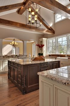 Rustic, gorgeous kitchen featuring vaulted ceilings, exposed wooden beams, a large island, marble countertops and ivory cabinets | Echelon Custom Homes