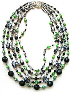 """A five-strand necklace in graduating lengths, each strand a different composition. A limited palette of greys, whites, and blacks highlight the the vibrant green """"eyeball"""" beads. There's a mixture of patterns as in the great kimono. A variety of beads, ceramic, vintage lucite, and glass with sterling silver accents as in the etched clasp."""