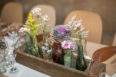 Rustic centerpiece - love the different bottles used for this #wedding.