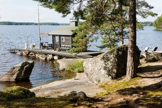 Pieni sauna nököttää veden päällä laiturilla. Kivikautiset siirtolohkareet rytmittävät maisemaa.