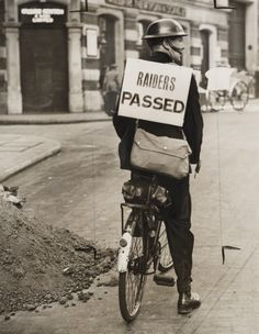 """""""A photograph of a Special Constable carrying a sign reading 'Raiders Passed' in the Strand, London, taken in September 1939 by an unknown photographer for the Daily Herald"""""""