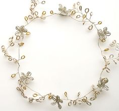 A wire, with bugle bead gold leaves, forms the base of the crown. Silver leaves and flowers were added.
