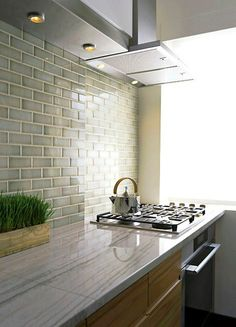 quartz counters, glass tile, warm cabinets
