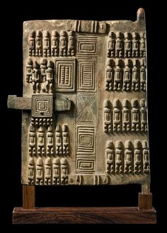 Africa | Granary door from the Dogon people of Mali | Wood, encrusted grey brown patina | ca. early to mid 1900s | granaries outnumber almost all other types of buildings in Dogon villages, demonstrating the importance of preserving crops produced with the hard labor required in such a rocky landscape. Every family has several granaries, one for each of the wives and the rest for the head of the family, in which are stored millet, sorghum, rice, corn, beans etc.