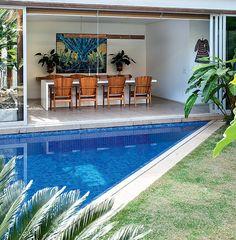 A piscina vai até a sala de jantar, integrada à área externa por painéis de correr. Projeto de paisagismo de Gil Fialho