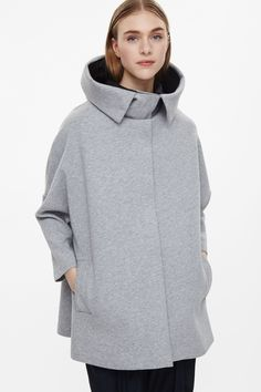 Designed with relaxed proportions, this cape is made from a soft cotton with a lightweight padding. An oversize fit, it has a zipped hood, dropped shoulders, front welt pockets and a hidden zip-up.