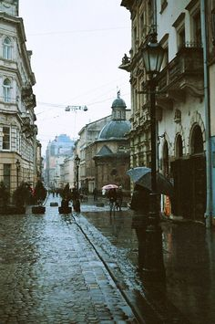 Lviv, UKRAINE. I would wear a bright blue or red coat and jump in the puddles.