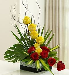 A year ago I was approached by 1800Flowers to come up with some designs. Their product code is 105093. Their price $84.99. A dozen yellow and red roses to symbolize love and friendship. Surrounded by lush tropical greens and placed in a contemporary black ceramic container wrapped in rhinestone ribbon. One sided. Container may vary.   $69.99
