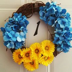 A easy $10 wreath! Bought two bushels of flowers: the blue & yellow and a $4.99 twig wreath. Then stuck the flowers around the wreath.