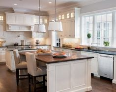 glass topped upper cabinets. white kitchen. dark (soapstone?) countertops. white backsplash.