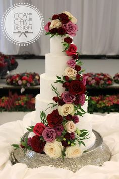 Rustic white iced wedding cake with fresh floral cascade in shades of burgundy, mauve and ivory.